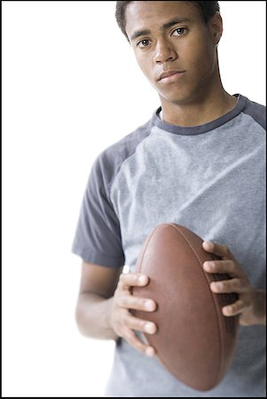 Portrait of a teenage boy holding a football Stock Photo - Premium Royalty-Free, Code: 640-01358139