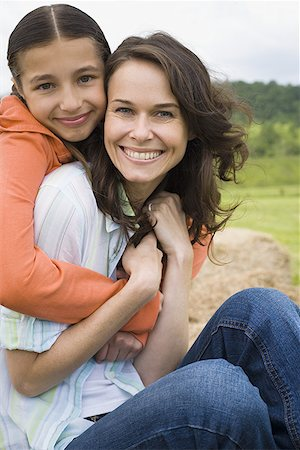Portrait of a girl hugging her mother from behind Stock Photo - Premium Royalty-Free, Code: 640-01358339
