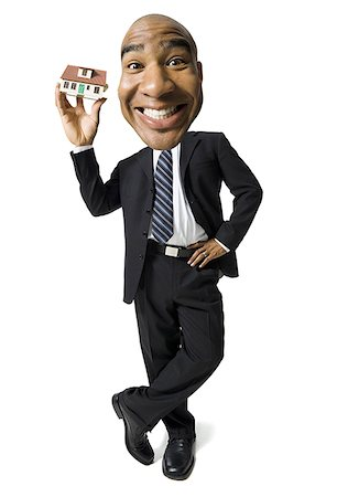 Businessman holding a little toy house Stock Photo - Premium Royalty-Free, Code: 640-01358331