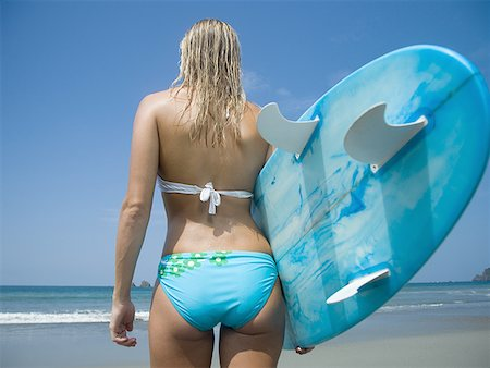 female rear end - Rear view of a young woman holding a surf board Stock Photo - Premium Royalty-Free, Code: 640-01358606
