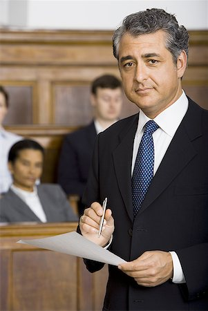 Portrait of a male lawyer standing in a courtroom during a trial Stock Photo - Premium Royalty-Free, Code: 640-01358689