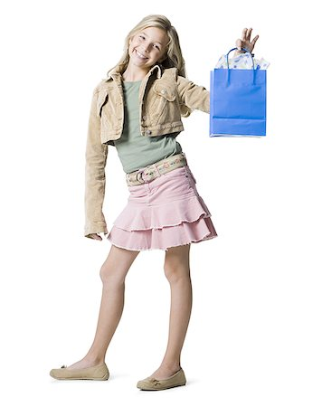 Portrait of a girl showing a shopping bag and smiling Stock Photo - Premium Royalty-Free, Code: 640-01358841