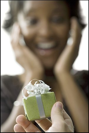Close-up of a person's hand holding a gift in front of a young woman Stock Photo - Premium Royalty-Free, Code: 640-01358874