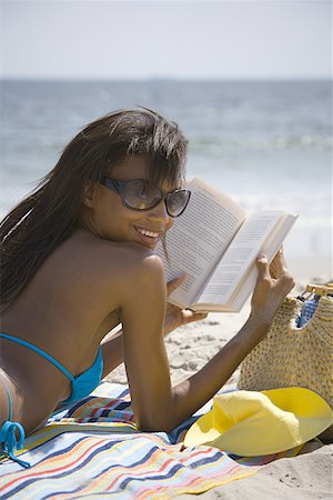 female rear end - Rear view of a young woman reading on the beach Stock Photo - Premium Royalty-Free, Code: 640-01358928
