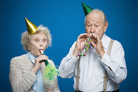 Older couple with noisemakers and party hats Stock Photo - Premium Royalty-Free, Code: 640-01358935