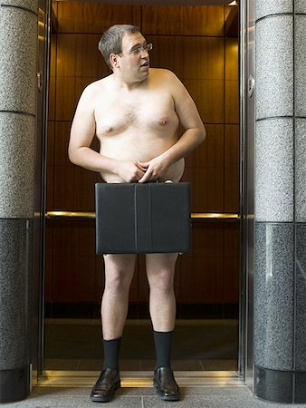 Naked businessman standing in front of an elevator and holding a briefcase Stock Photo - Premium Royalty-Free, Code: 640-01359061