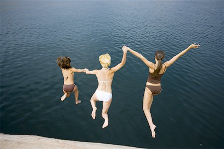 female rear end - High angle view of three young women jumping into a lake Stock Photo - Premium Royalty-Free, Code: 640-01359241