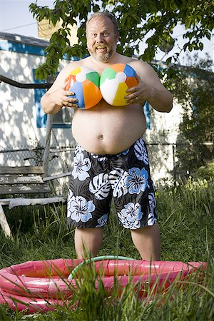 Overweight man by inflatable wading pool Stock Photo - Premium Royalty-Free, Code: 640-01359250