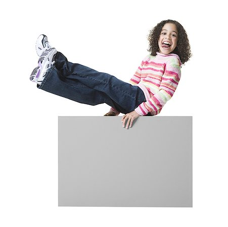 Portrait of a girl sticking her tongue out and sitting on a blank sign Stock Photo - Premium Royalty-Free, Code: 640-01359409