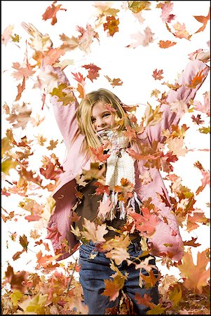 pile leaves playing - Young girl playing in fallen leaves Stock Photo - Premium Royalty-Free, Code: 640-01359402