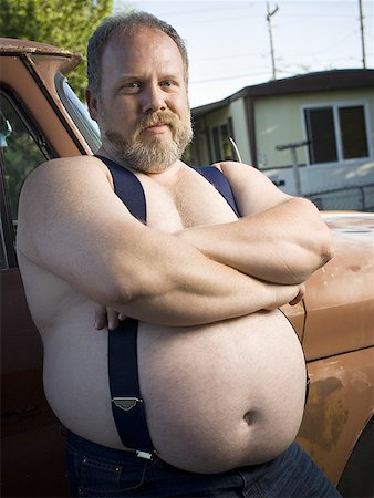 Overweight man with suspenders by truck Stock Photo - Premium Royalty-Free, Code: 640-01359483