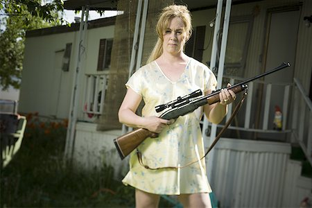 Woman in trailer park with a rifle Stock Photo - Premium Royalty-Free, Code: 640-01359984