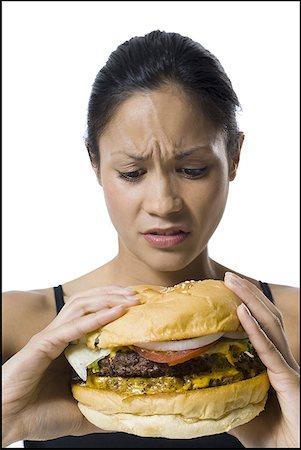 Woman eating a supersized hamburger Stock Photo - Premium Royalty-Free, Code: 640-01350060