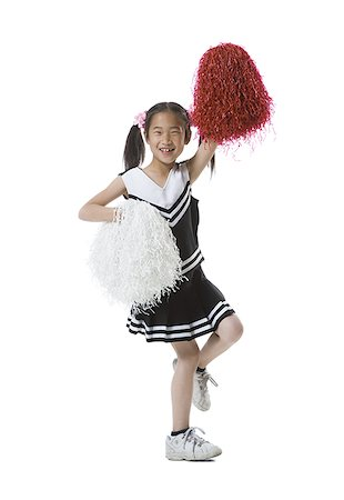 Portrait of a cheerleader dancing with pom-poms Stock Photo - Premium Royalty-Free, Code: 640-01350336