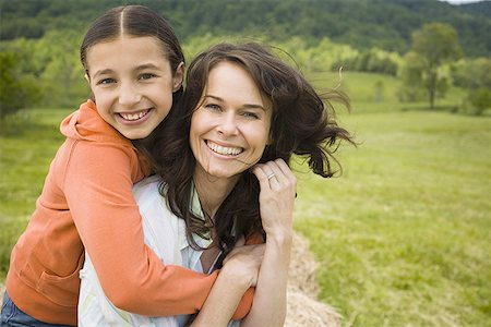 Portrait of a girl hugging her mother from behind Stock Photo - Premium Royalty-Free, Code: 640-01350617