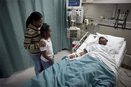 High angle view of a mother and daughter in a hospital looking at a teenage boy Stock Photo - Premium Royalty-Free, Code: 640-01350692