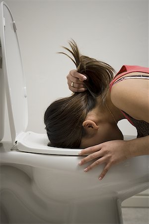 Profile of a young woman vomiting into a toilet bowl Stock Photo - Premium Royalty-Free, Code: 640-01350940