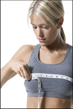 A young woman measuring her chest with a measuring tape Stock Photo - Premium Royalty-Free, Code: 640-01351372