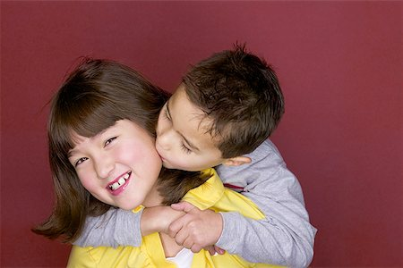 preteen kissing - Portrait of a sister being kissed by her brother Stock Photo - Premium Royalty-Free, Code: 640-01351521