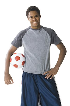 Portrait of a teenage boy with a football under his arm Stock Photo - Premium Royalty-Free, Code: 640-01351571