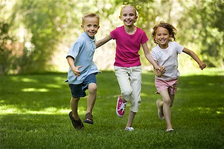 Portrait of three children running Stock Photo - Premium Royalty-Free, Code: 640-01351707