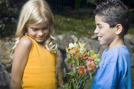 Profile of a boy giving flowers to a girl and smiling Stock Photo - Premium Royalty-Free, Code: 640-01351748