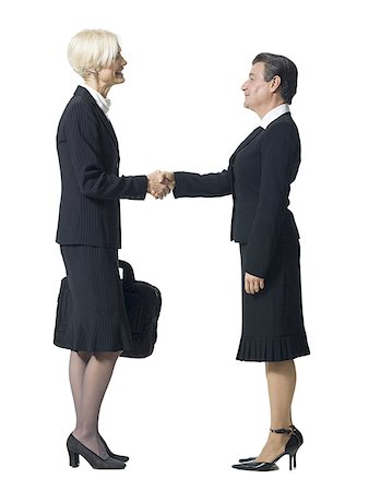 Mature businesswoman shaking hands with businesswoman with man's head Stock Photo - Premium Royalty-Free, Code: 640-01351837
