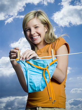 Portrait of a teenage girl drying a bikini bottom on a clothesline Stock Photo - Premium Royalty-Free, Code: 640-01351903