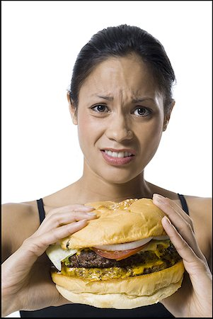 Woman eating a supersized hamburger Stock Photo - Premium Royalty-Free, Code: 640-01352162