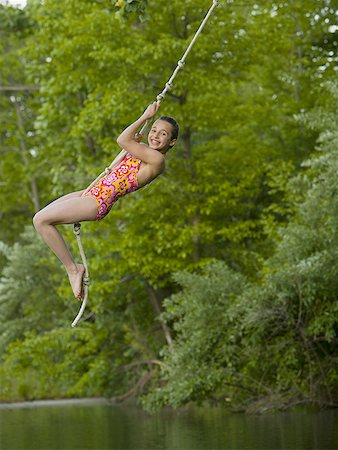 Portrait of a girl swinging on a rope Stock Photo - Premium Royalty-Free, Code: 640-01352202