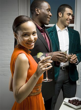 represented - Portrait of a young woman holding glass of a wine with two mid adult men standing beside her Stock Photo - Premium Royalty-Free, Code: 640-01352553