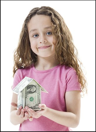 Portrait of a girl holding a house of paper money Stock Photo - Premium Royalty-Free, Code: 640-01352592