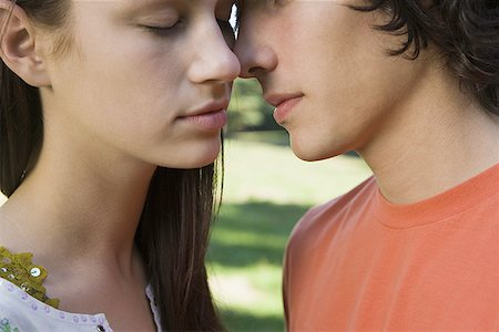 Close-up of a teenage couple kissing each other Stock Photo - Premium Royalty-Free, Code: 640-01352602