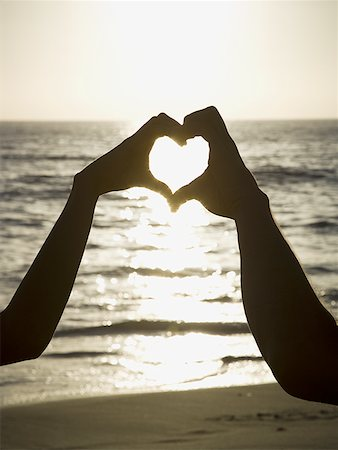 female silhouettes heart - Couple on a beach making a heart symbol with their hands Stock Photo - Premium Royalty-Free, Code: 640-01352670