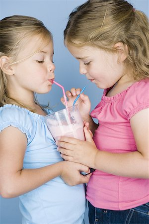 Close-up of two sisters sharing a milkshake Stock Photo - Premium Royalty-Free, Code: 640-01352724