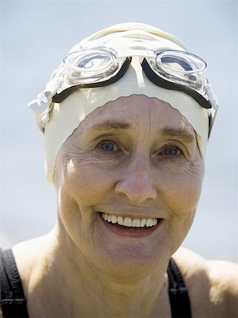 Mature woman with swimming cap and goggles smiling Stock Photo - Premium Royalty-Free, Code: 640-01352759