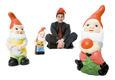 dwarf - Portrait of a businessman sitting with three garden gnomes Stock Photo - Premium Royalty-Free, Code: 640-01352901