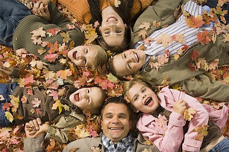 pile leaves playing - Young girls playing in pile of fallen leaves Stock Photo - Premium Royalty-Free, Code: 640-01353098