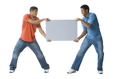 Two young men fighting over a blank sign Stock Photo - Premium Royalty-Free, Code: 640-01353388