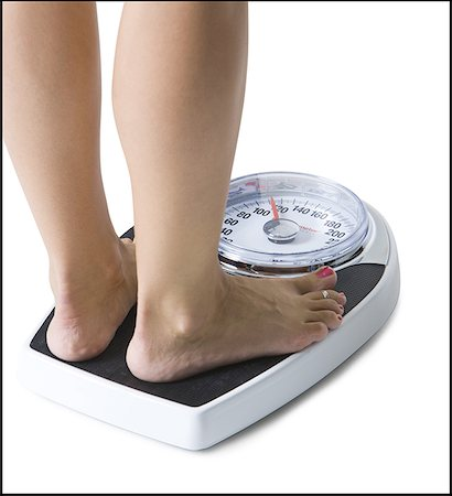 female rear end - Feet standing on a bathroom scale Stock Photo - Premium Royalty-Free, Code: 640-01353414