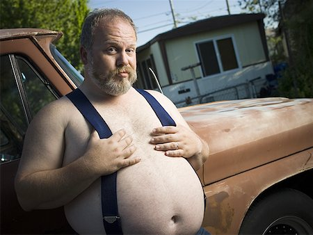Overweight man with suspenders by truck Stock Photo - Premium Royalty-Free, Code: 640-01353419