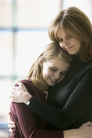 Close-up of a mother hugging her daughter Stock Photo - Premium Royalty-Free, Code: 640-01353426