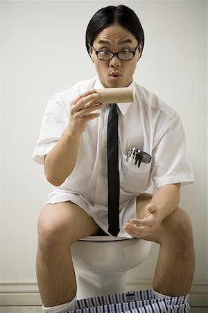 Close-up of a young man sitting on a toilet Stock Photo - Premium Royalty-Free, Code: 640-01353427