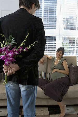 pregnant couple couch - Rear view of a man holding flowers and looking at a pregnant woman Stock Photo - Premium Royalty-Free, Code: 640-01353444