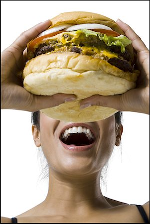 Woman eating a supersized hamburger Stock Photo - Premium Royalty-Free, Code: 640-01353465