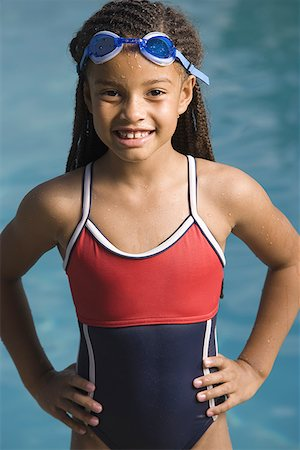 Portrait of a girl standing at a swimming pool and smiling Stock Photo - Premium Royalty-Free, Code: 640-01353482