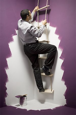 running away scared - Rear view of a businessman climbing a ladder Stock Photo - Premium Royalty-Free, Code: 640-01353925