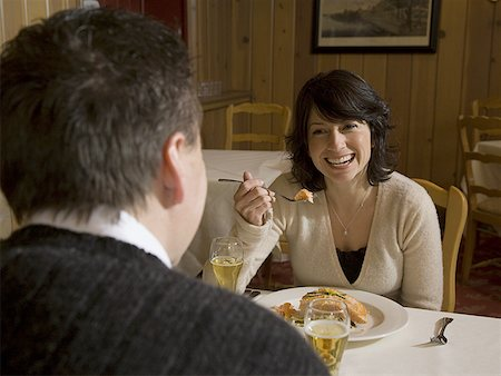 female rear end - Mid adult woman eating food in front of a mid adult man Stock Photo - Premium Royalty-Free, Code: 640-01353953