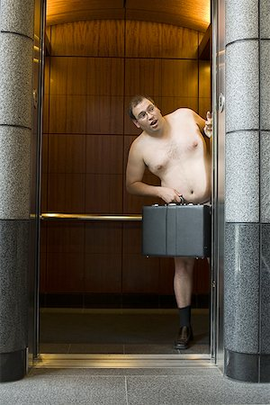 Naked businessman standing in an elevator and holding a briefcase Stock Photo - Premium Royalty-Free, Code: 640-01364192