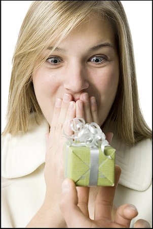 Close-up of a person giving a gift to a young woman Stock Photo - Premium Royalty-Free, Code: 640-01364467